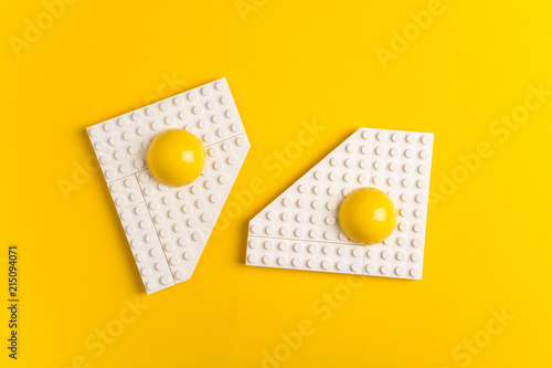 Top view of white plate with fried eggs of children's designer on yellow paper background. Good