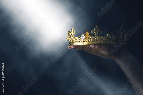 mysteriousand magical image of woman's hand holding a gold crown over gothic black background Fototapeta