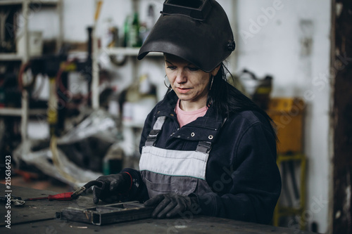Strong and worthy woman welder doing hard job in car and motorcycle repair shop. She using welding machine to fix some metal bike parts.