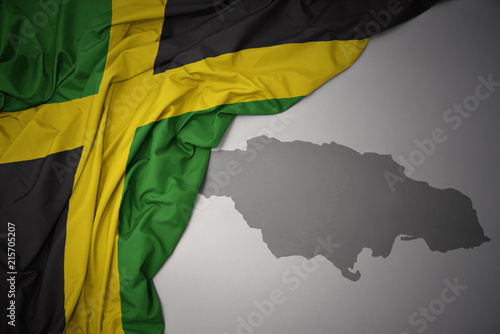 Wallpaper Mural waving colorful national flag and map of jamaica.