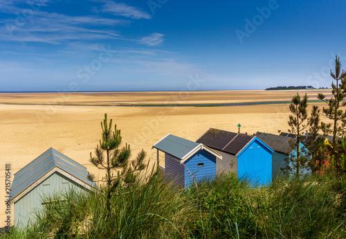 Obraz na płótnie seaside beach huts at low tide against beautiful beach and blue sky, Wells Next