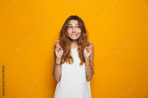 Portrait of an excited young girl holding fingers crossed Fototapet
