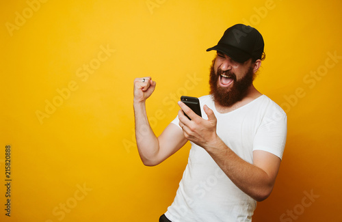 Slika na platnu Happy bearded man celebrate success and looking at phone