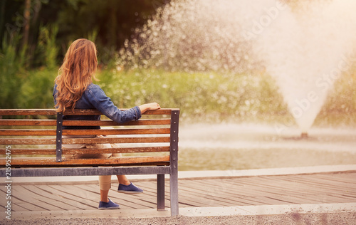 Tablou Canvas Young woman sitting on bench in park