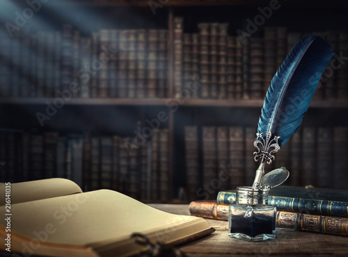 Old quill pen, books and vintage inkwell on wooden desk in the old office against the background of the bookcase and the rays of light. Retro style.
