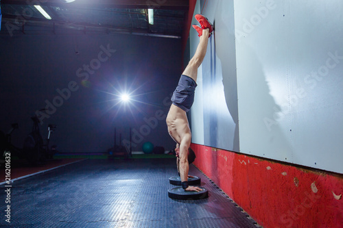 Canvas-taulu Photo of a young fit man doing a handstand exercise at a Cross style fit