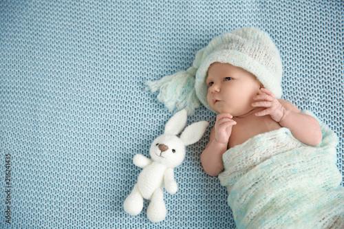 Cute newborn baby girl lying on plaid