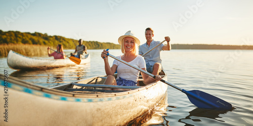 Canvas Print Smiling woman canoeing with friends on a lake in summer