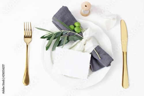 Festive table summer setting. Golden cutlery, olive branch, linen napkin, porcelain dinner plate and silk ribbon on white table background. Blank card mockup. Mediterranean wedding or restaurant menu