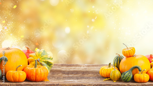 pile of orange pumpkins on wooden table over fall background banner