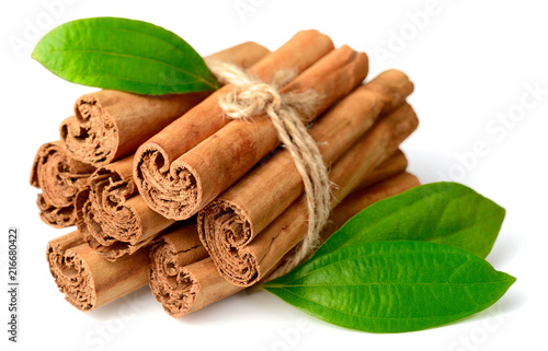 Canvas-taulu bunch of cinnamon sticks with fresh leaves isolated on the white background