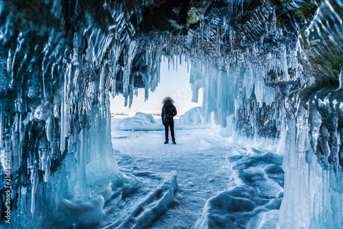 Fototapeta Travelling in winter,  a man standing on Frozen lake Baikal with Ice cave in Irk