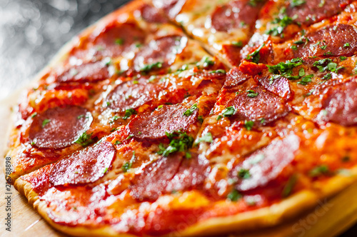 Fototapeta sliced Pepperoni Pizza with Mozzarella cheese, salami, Tomatoes, pepper, Spices and Fresh Basil