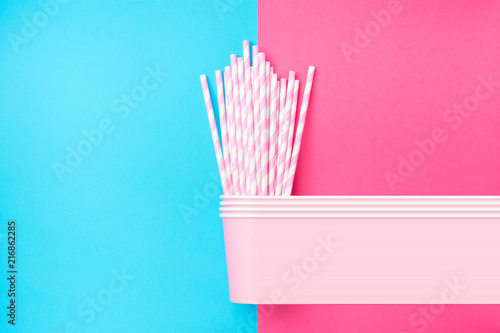 Stacked Drinking Paper Cups with Striped Straws on Duo Tone Light Blue Pink Background. Flat Lay. Birthday Party Celebration Kids Fun. Greeting Card Poster Template. Copy Space. Pixel stretch glitch