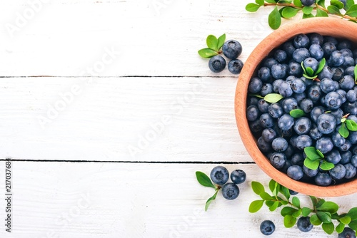 Blueberries with leaves in a wooden plate Fototapeta