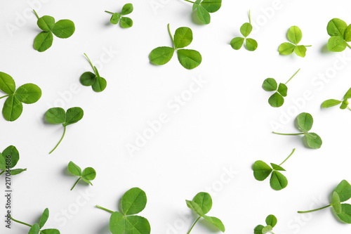 Fotografía Green clover leaves on white background, flat lay composition with space for tex
