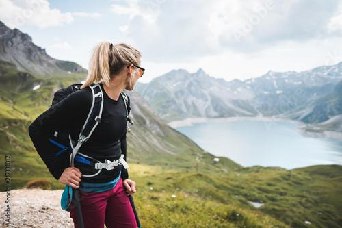 Fototapeta Adventurous Sportive Girl hiking at a Lake in Beautiful Alpine Mountains
