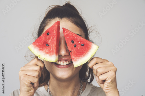 Young woman holding watermelon slices popsicles on her eyes