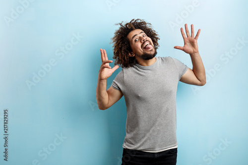 A curly-headed handsome man wearing a gray T-shirt is having fun with his tongue out, playful eyes and palms open and raised over the blue background Fototapeta