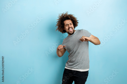 Fotografija A curly-headed handsome man wearing a gray T-shirt is standing with a cheerful smile and dancing with his eyes closed over the blue background