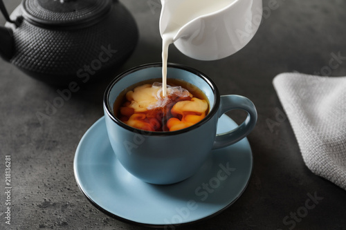 Pouring milk into cup of black tea on table