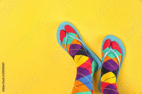 Woman wearing bright socks with flip-flops and space for design on color background