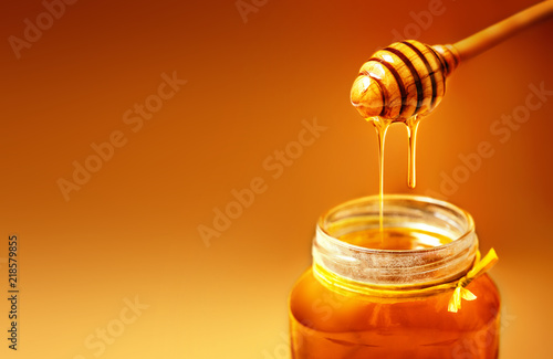 Photo Honey in jar with honey dipper on rustic wooden table background