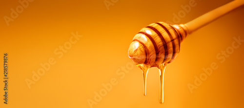 Canvas Print Honey dripping from wooden honey dipper over  yellow background