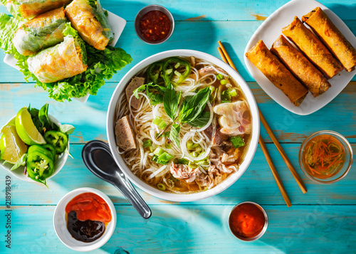 vietnamese beef pho bo soup in bowl on table top with spring rolls and appetizers