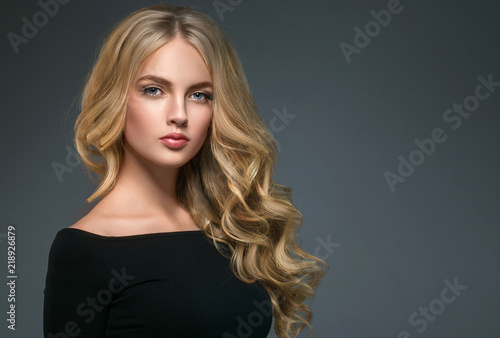 Blonde hairstyle woman beauty with long curly blonde hair over dark background Fototapeta