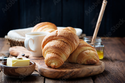 Fotografia Delicious breakfast with fresh croissants and coffee served with butter and honey