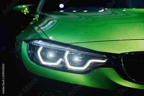 Closeup headlights of modern car during turn on light in night.