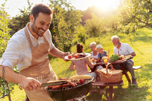 Foto Happy family having barbecue party in backyard