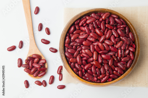 Red beans in wooden bowl and spoon putting on linen and white background.