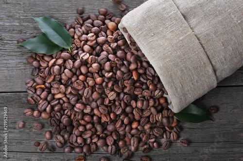 Fotografía Coffee beans in burlap sack on wood background