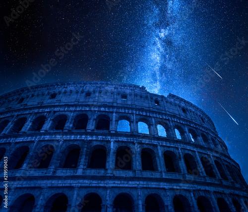 Fototapeta premium Oszałamiające Koloseum w Rzymie nocą z spadającymi gwiazdami, Włochy