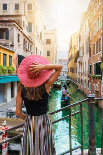 Fototapeta premium Elegancka kobieta z czerwonymi słońce kapeluszu spojrzeniami na kanale z przelotną gondolą w Wenecja, Włochy