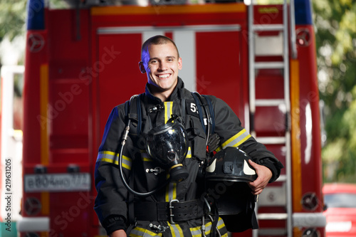 Canvas Print Photo of happy fireman with gas mask and helmet near fire engine