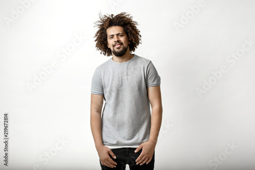 Fotografija A curly-headed handsome man wearing a gray T-shirt is standing slightly smiling over the white background