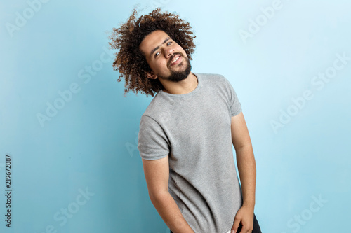 Slika na platnu A curly-headed handsome man wearing a gray T-shirt is standing, leaning to the right, with a romantic look over the blue background