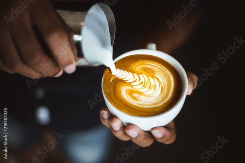 Foto Barista making a cup of coffee latte art.