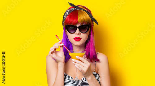 Young girl with purple hair holding lemonade cocktail on yellow background