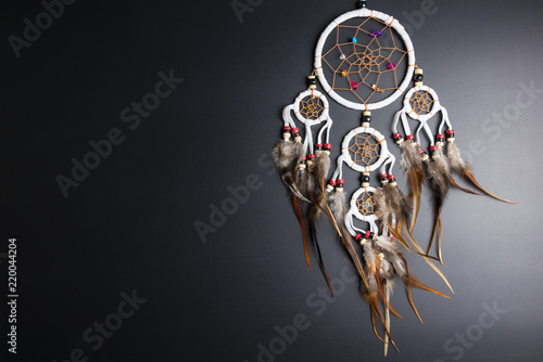 Photo Dream catcher with feathers threads and beads rope hanging spiritual folk american native indian amulet isolated on black background