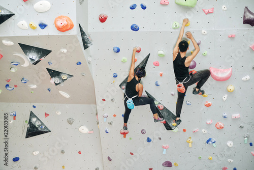 Canvas Print Couple enjoying climbing on artificial wall in gym