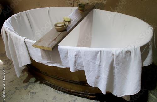 Fotografía baignoire en bois garnie d'un drap et accessoires de bain comme au moyen âge