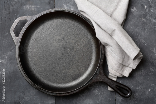 Empty, clean black cast iron pan or dutch oven top view from above on black table with towel