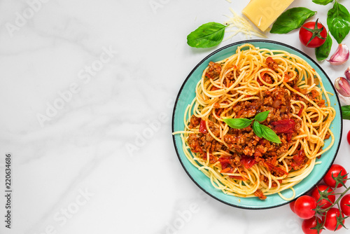 pasta spaghetti bolognese on a blue plate on white marble table. healthy food. view from above