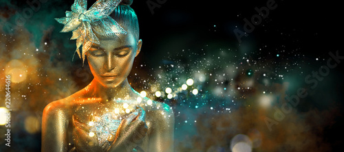 Fashion model woman in colorful bright golden sparkles and neon lights posing with fantasy flower. Portrait of beautiful girl with glowing makeup