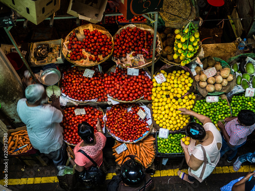 Canvas Print people buying food, fruit and vegetables at a stall in traditional central marke