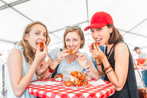 Group of young multiracial girl friends eating seafood crab or crawfish at a outdoor restaurant